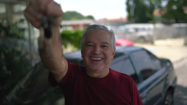 Portrait of senior man showing car keys Portrait of senior man showing car keys car key stock videos & royalty-free footage