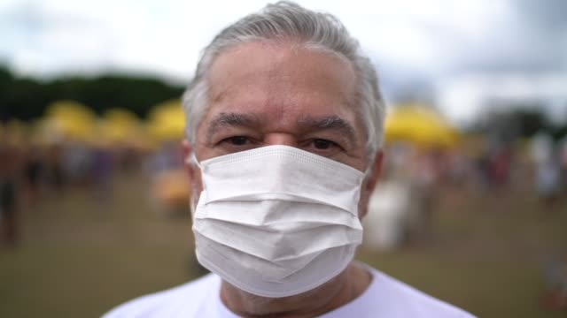 portrait of senior man with facial mask in a public event - face mask stock videos & royalty-free footage