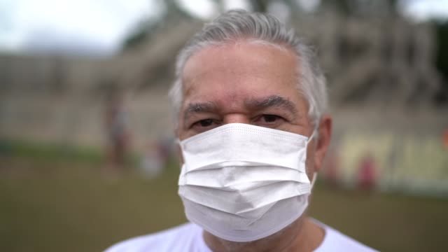 Portrait of senior man with facial mask in a public event