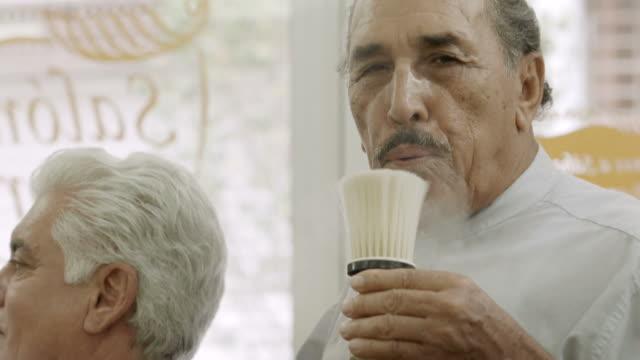 vidéos et rushes de portrait d'homme senior travaillant comme coiffeur dans un salon de coiffure - salons et coiffeurs