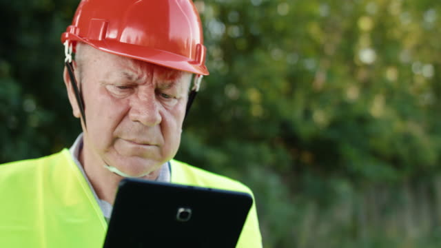 Portrait of senior railroader in uniform types on tablet and looks aside camera video