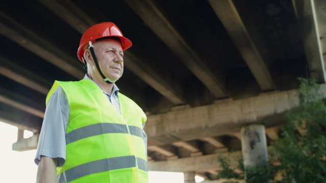 Portrait of senior railroader looking into the distance and correcting helmet video