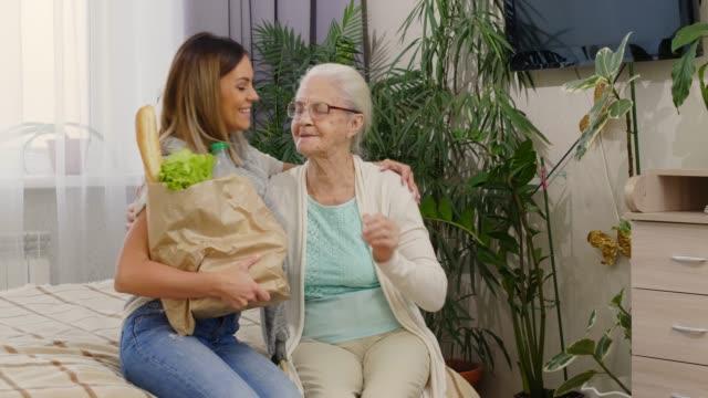 ritratto di donna anziana e volontaria donna con borsa della spesa - grocery home video stock e b–roll