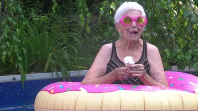 havuz yaz şenlikli tutum tarafından dondurma enjoy senior woman portresi - eksantrik stok videoları ve detay görüntü çekimi