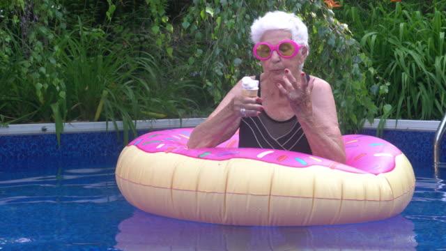 vídeos y material grabado en eventos de stock de retrato de mujer mayor disfrutando de helados por la piscina verano actitud festiva - ice cream