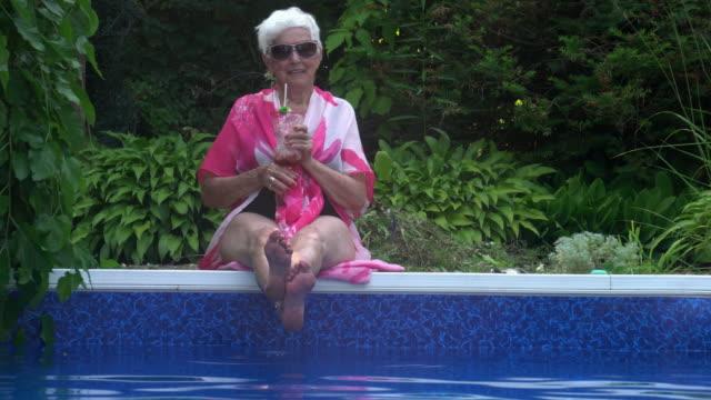 havuz tarafı yaz şenlikli tutum tarafından yaşam zevk kıdemli kadın portresi - eksantrik stok videoları ve detay görüntü çekimi