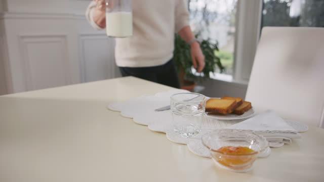 Portrait of senior woman having breakfast with milk video