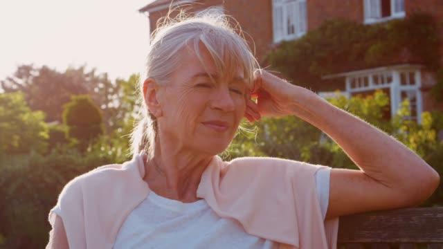 vídeos de stock e filmes b-roll de portrait of senior woman sitting on garden bench in evening - old lady