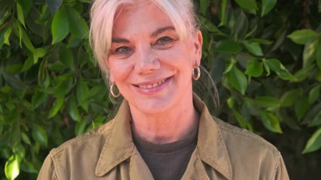 bitki karşı gülümseyen kıdemli kadının portresi - yalnızca yetişkinler stok videoları ve detay görüntü çekimi