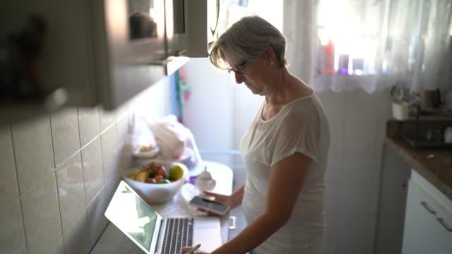 vídeos de stock e filmes b-roll de portrait of senior woman using laptop at kitchen - 55 59 anos
