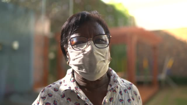 vídeos de stock e filmes b-roll de portrait of senior woman wearing face mask at home - afro latino mask