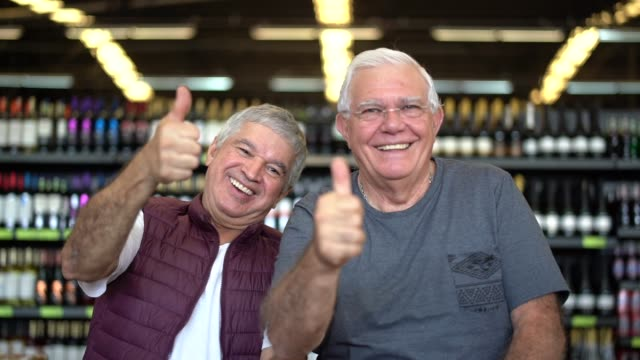 Portrait of seniors at the supermarket making positive gesture Portrait of seniors at the supermarket making positive gesture baby boomers stock videos & royalty-free footage