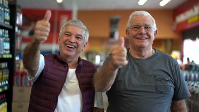 Portrait of seniors at the supermarket making positive gesture