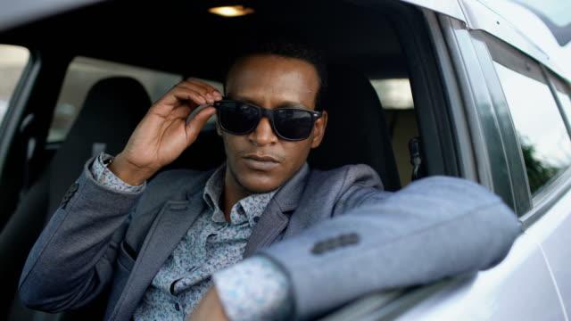 porträtt av seriös affärsman sitter inne i bilen sätta solglasögon och ler in i kameran utomhus - solglasögon bildbanksvideor och videomaterial från bakom kulisserna