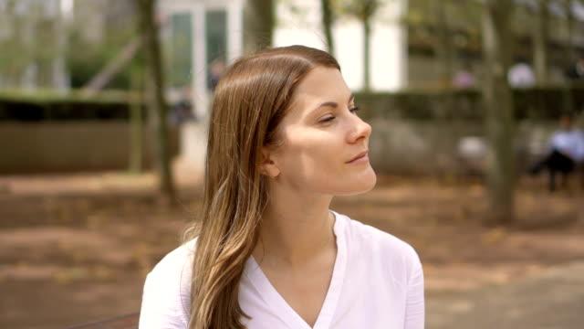 Retrato de empresaria seria en camisa blanca, sentado en el parque. Profesional femenino con rotura - vídeo