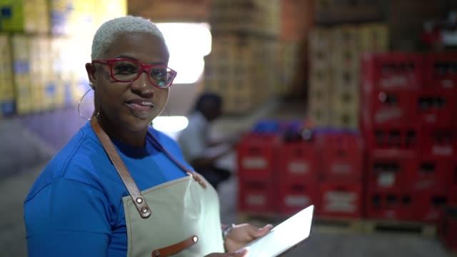 portrait of serious employee using digital tablet at warehouse - prodotti supermercato video stock e b–roll