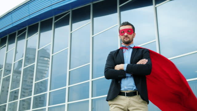Portrait of serious office worker in red superhero cape and mask standing outside video