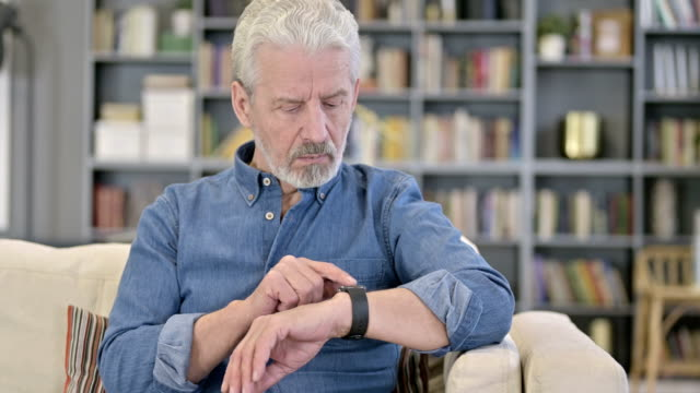 portrait of serious old man using smartwatch - computer indossabile video stock e b–roll