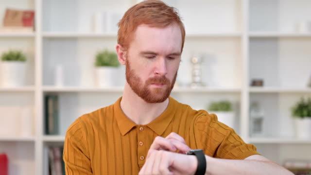 portrait of serious redhead man using smart watch - staw człowieka filmów i materiałów b-roll