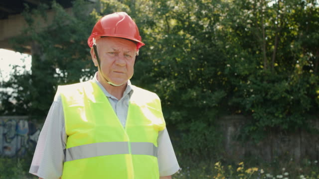 Portrait of serious senior engineer in uniform and helmet looks into the camera video