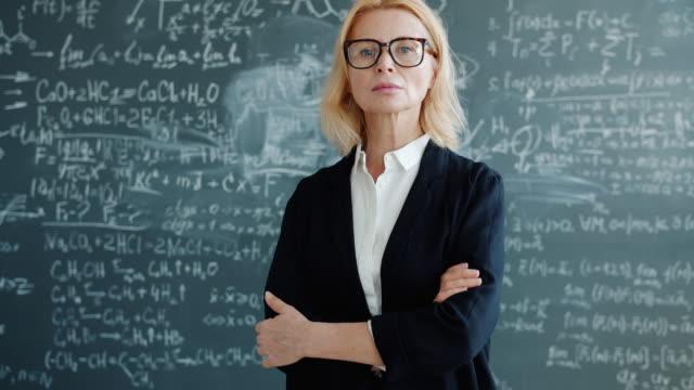 porträt einer seriösen smarten professorin im klassenzimmer mit formeln an der tafel - vorlesungsfrei stock-videos und b-roll-filmmaterial