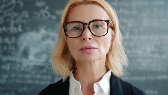 porträt einer seriösen wissenschaftlerin in brille, die in der universitätsklasse in die kamera schaut - vorlesungsfrei stock-videos und b-roll-filmmaterial