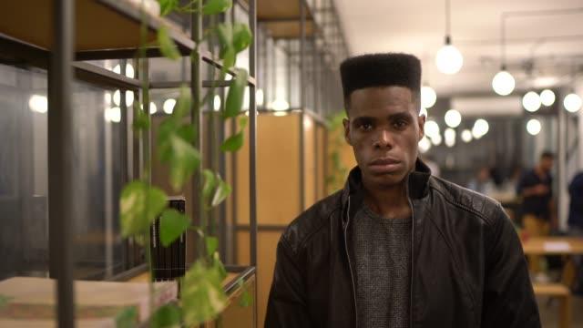 vídeos de stock, filmes e b-roll de retrato do homem de negócios novo sério no escritório creativo - brasileiro pardo