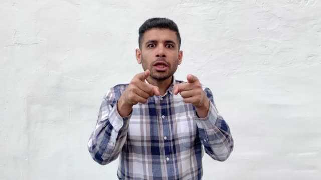 Portrait of shcoked bearded man in blue checkered shirt standing, pointing and looking at camera with surprised unbelievable happy amazed face.