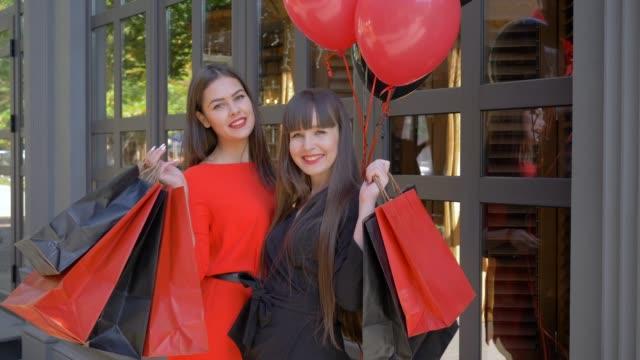 vídeos y material grabado en eventos de stock de retrato de las niñas de los compradores, sonriendo novias levantar bolsas de compras y disfrutar de éxito compras en las tiendas durante negro el viernes - black friday sale