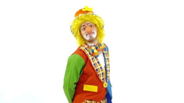 Portrait of shy clown in colorful hat giving a box as a present video