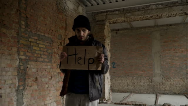 Portrait of sick dirty homeless with table 'help' video