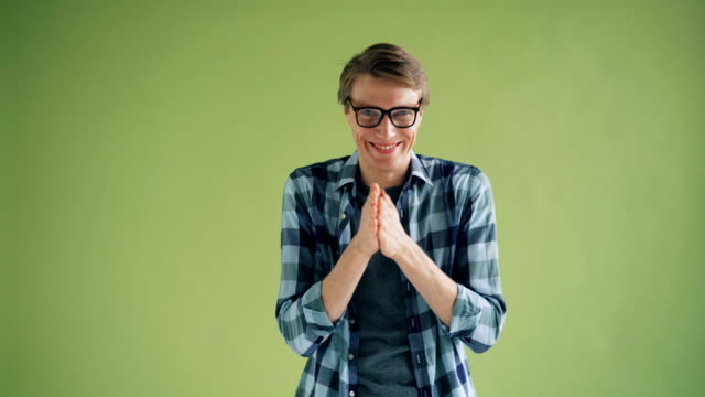 Video Portrait of sly young man rubbing his hands and smiling looking at camera