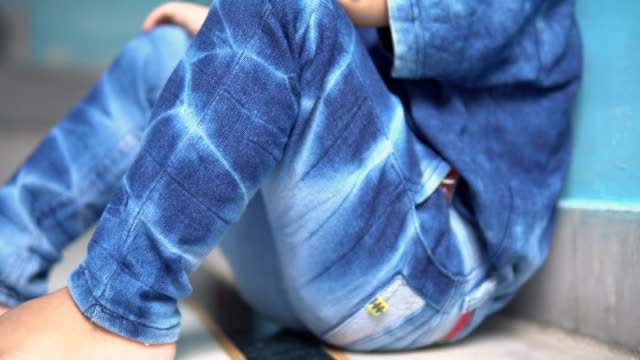 portrait of small boy wearing blue jeans and t-shirt