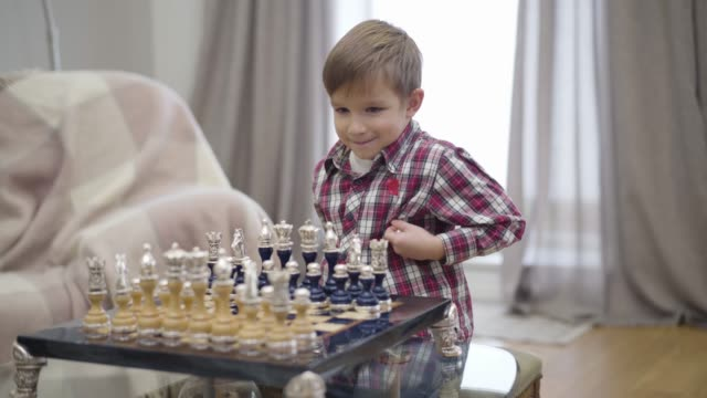 Portrait of smart Caucasian boy setting chess pieces on board. Little cute child starting playing with unrecognizable father. Intellect, intelligence.