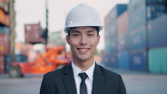Portrait of smile asian businessman or engineer age 27 yearold looking at camera of confidence at commercial transport background.Pride in Work concept.