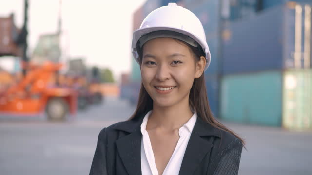 Portrait of smile asian businesswoman or female engineer age 25 yearold looking at camera of confidence at commercial transport background.Pride in Work concept.