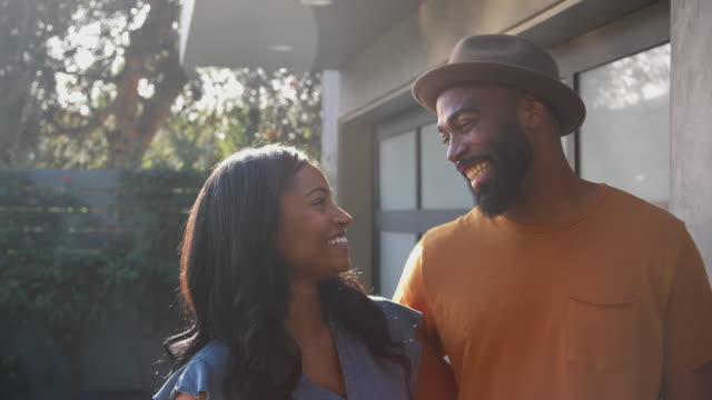 Portrait Of Smiling African American Couple Talking And Laughing In Garden At Home