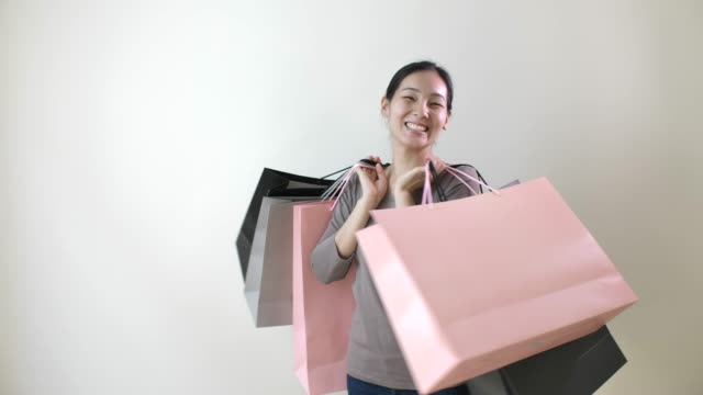 portrait of smiling asian beautiful woman carrying shopping bags in hand - borsa della spesa video stock e b–roll