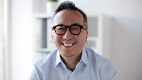 vidéos et rushes de portrait d'une homme d'affaires asiatique souriante au bureau - portrait