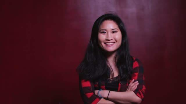 portrait of smiling asian woman folding arms - 30 34 anni video stock e b–roll