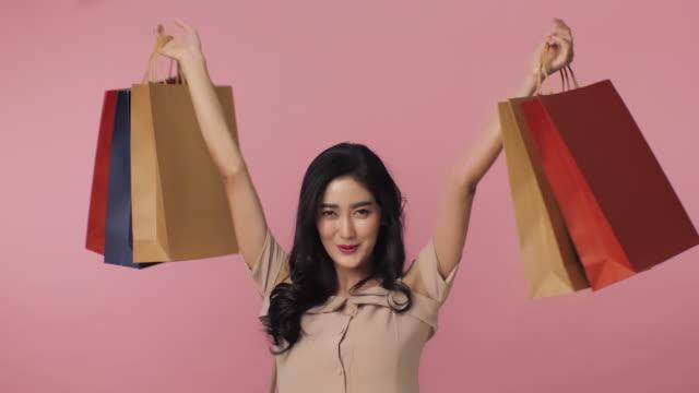ピンクの背景のスタジオでアジアの女性を笑顔の肖像画。幸せな女は、カラフルなバッグをショッピングの多くを保持しています。季節の販売コンセプト。 - 通販点の映像素材/bロール