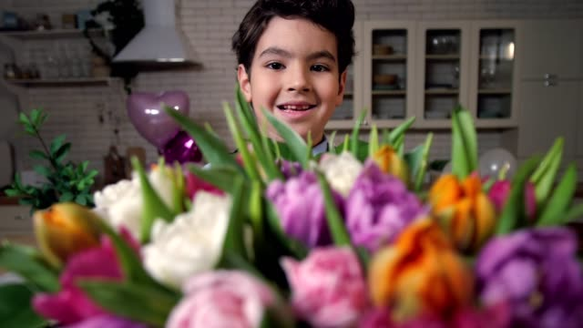 portrait of smiling boy with bouquet of flowers - mothers day stock videos & royalty-free footage