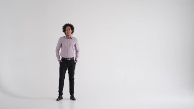 portrait of smiling businessman in studio - mani sui fianchi video stock e b–roll