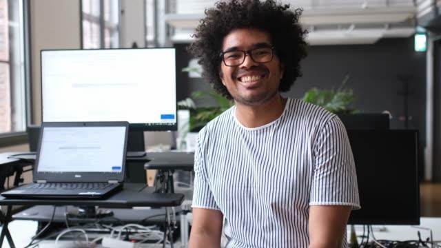 stockvideo's en b-roll-footage met portret van glimlachende zakenman zittend aan het bureau - 25 29 jaar