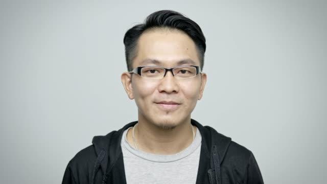 vídeos de stock, filmes e b-roll de retrato de eyeglasses desgastando de sorriso do homem de negócios - fundo branco