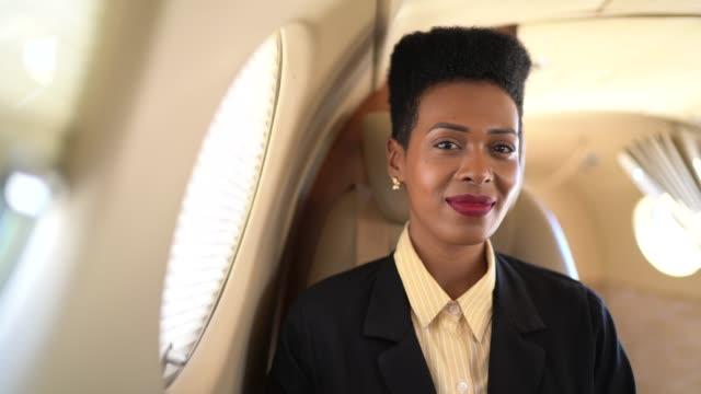 企業のジェット機でカメラを見ている笑顔のビジネスウーマンの肖像 - 豊かなライフスタイル点の映像素材/bロール