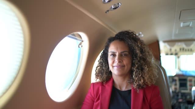 기업 제트기에서 카메라를 바라보는 미소 짓는 사업가의 초상화 - airplane seat 스톡 비디오 및 b-롤 화면