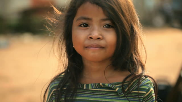 Portrait of smiling Cambodian girl Portrait. Smiling face of a cute rural girl turning to the camera, Beautiful light with wind in her hair. Age 5. Taken in Cambodia, Asia, poverty stock videos & royalty-free footage