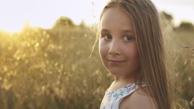 ritratto di sorridente bambina caucasica che guarda la macchina fotografica nella natura - grano graminacee video stock e b–roll