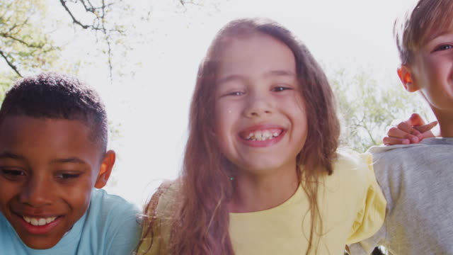 Portrait of smiling children outdoors in garden standing in a line - shot in slow motion